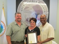 Holding a Citrus Heights city council proclamation in recognition of Building Safety Month, Susan McLendon and Greg Anderson from the building department stand with Mayor Mel Turner (right).