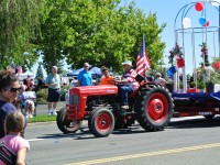 """A tractor pulls a float at the 2014 """"Red, White & Blue"""" Parade."""