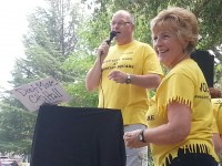 Tim Schaeffer, with Save City Hall, speaks at Sunday's rally in Rusch Park, joined by resident Joan Bippus on the right.