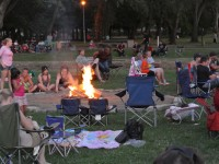 Campers gather around a fire and listen to live music at Rusch Park, Saturday night.