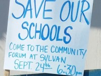A sign posted near Sylvan Middle School invites residents to the community forum on Wednesday night.