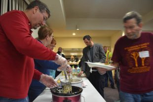 Volunteers serve homeless guests a hot meal at a local church as part of a local winter shelter program. // CH Sentinel