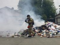 A firefighter douses a pile of garbage that caught fire in the back of a garbage truck in Citrus Heights. // Photo credit: Metro Fire
